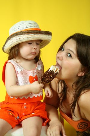 Two pretty sisters are eating ice-cream on yellow background