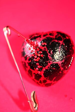 A red heart with a safety pin through it, bleeding..... broken, wounded  heart photo