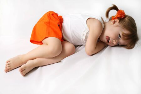 Small girl is tired against the white background photo