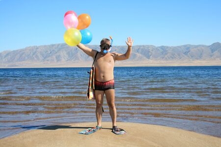comically: Man with mask, flippers and balloons is salutation  on the beach