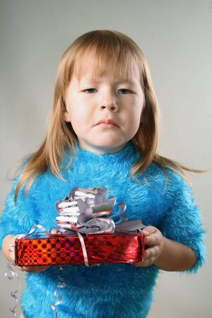 bummed: Young girl with unpleasant gift over grey background