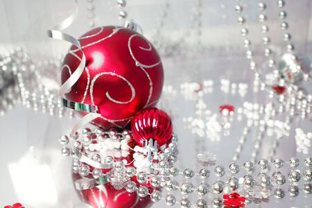 A lovely red baubles on a mirror  surface with ribbons and beads. photo