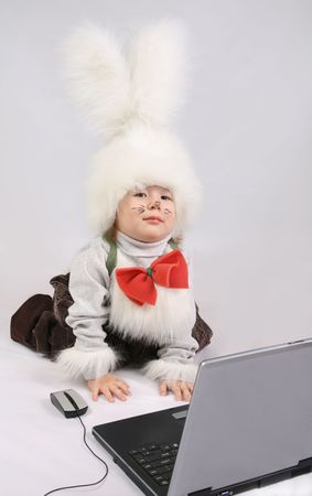 Child in a white downy bunny costume before laptop photo