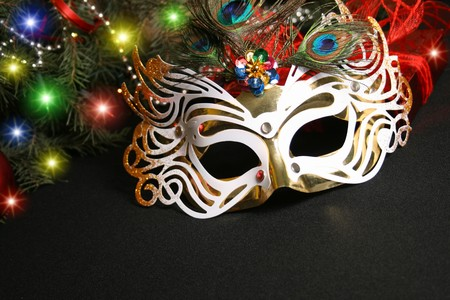 Mask and Christmas light. Carnival the mask is isolated on a black background Stock Photo