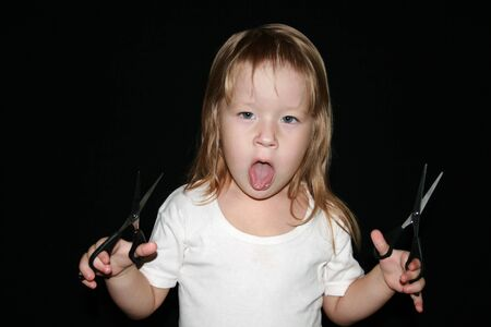 long tongue: Little girl with scissors. Black background. Stock Photo
