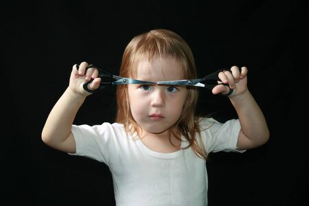 Little girl with scissors. Black background. photo