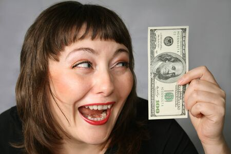 herself: Woman with hand of money, looking Ecstatic with herself on a Black background.