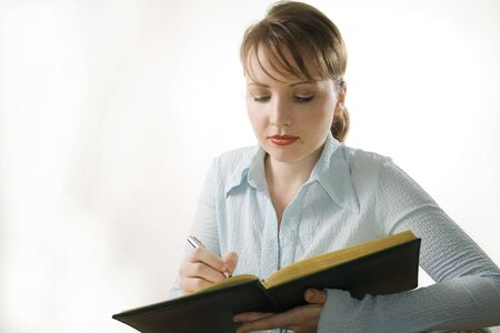 Young woman is writing something and thinking  photo