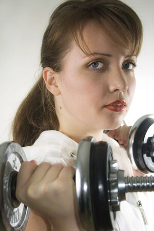 A young  woman uses a dumbbell for weight training exercises. photo