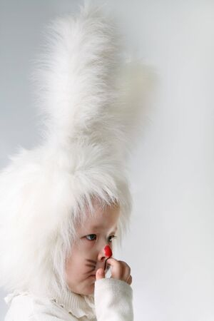 little girl in a white downy bunny costume.