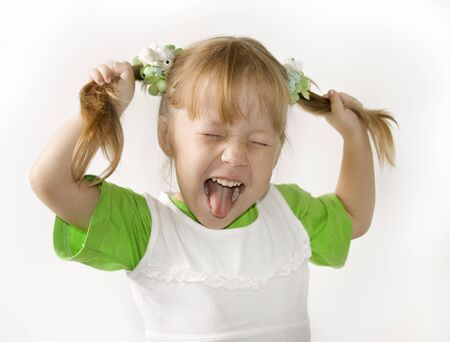 playful behaviour: Head and hands shot of Little girl sticking out her tongue at the camera for fun