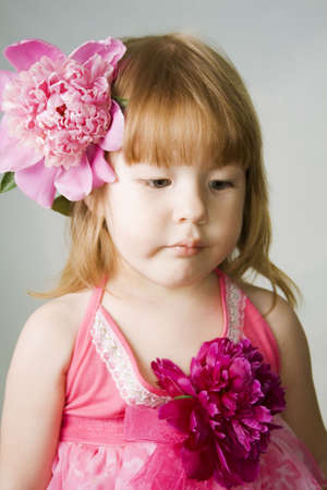 pion: Little sad girl holding the red pion in her mouth Stock Photo