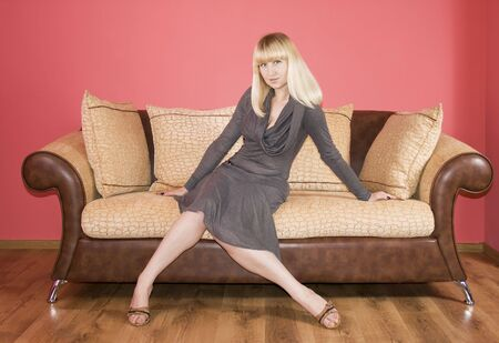 Blond girl sits on the sofa against the background of the red wall photo