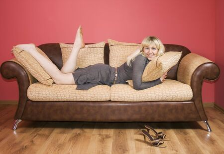 Blonde woman lies on the sofa barefoot photo