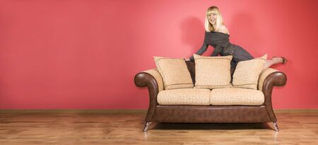 Blonde merry girl on top of the sofa photo