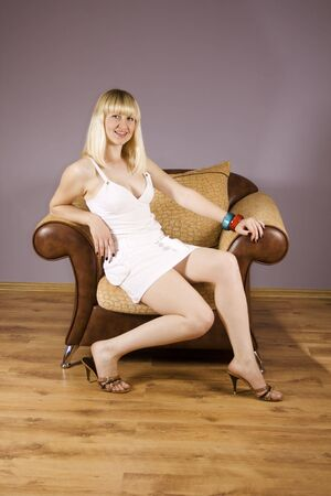 Beautiful  blond woman relaxing in elegance armchair photo