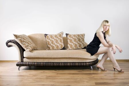 Blond girl sits on the sofa against the background of the white wall photo