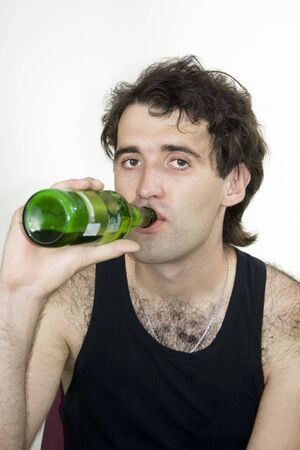 A nice young man drinks beer bottle  photo