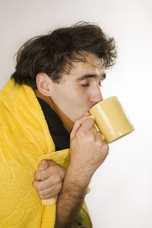 Young man drinks hot tea and hopes to become well Stock Photo