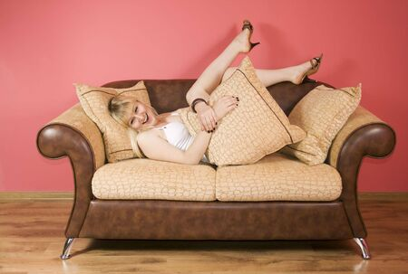 lying down happy blond woman on a couch photo