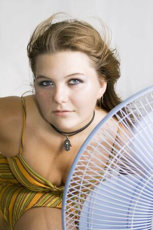 The fan blows to face of woman photo