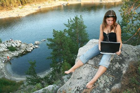Young girl with laptop on Outdoors photo