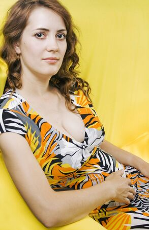 Pregnant  young women be sitting at the yellow sofa. photo