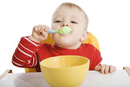 Little boy eating breakfast isolated on white.