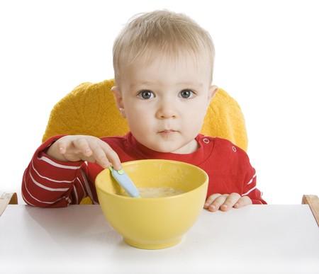 disciplined: Little boy eating breakfast isolated on white.