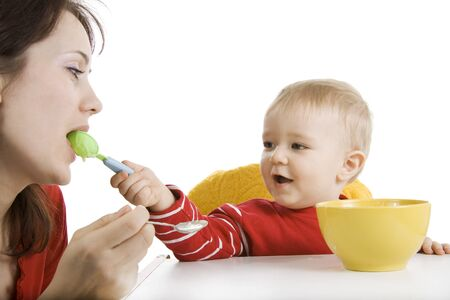 The small son feeds the mother from a spoon photo