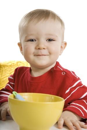 Little boy eating breakfast isolated on white. Stock Photo - 7291679