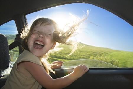 extase: Beetje leuk meisje snelheden in auto in de buurt van het geopende venster.
