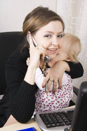 padres hablando con hijos: madre ocupada manteniendo su beb�  Foto de archivo