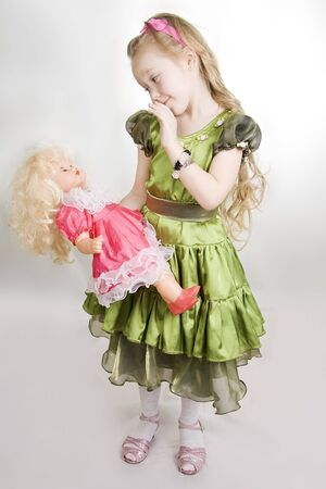 The little girl plays with a doll. photo