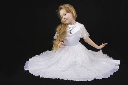 curtsy: The girl the princess in a white dress sits opposite to a black background Stock Photo