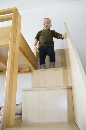 home safety: The little boy costs at a step and looks downwards
