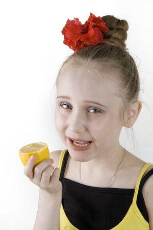 poco: Una niña bonita comiendo un limón