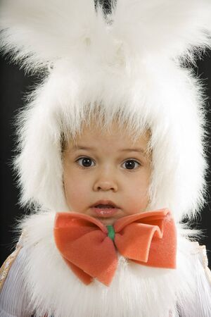 �hild in a white downy bunny costume. photo