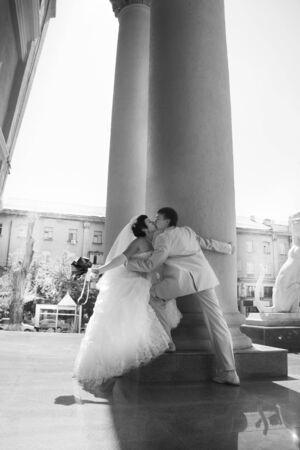 Groom and bride kiss near Wedding palace photo