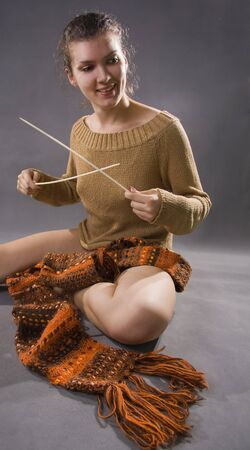 The young woman on spokes knits a scarf. On a gray background. photo