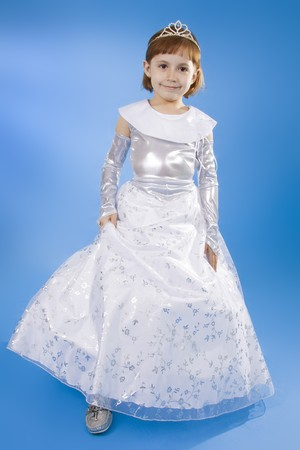 The girl the princess in a white dress sits opposite to a blue background Stock Photo - 7968084