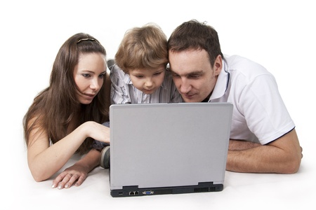 Young family lying on a floor with the computer on white isolation Stock Photo - 8612464