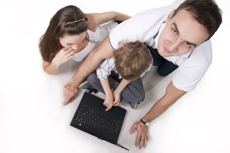 Young family lying on a floor with the computer on white isolation Stock Photo - 8612462