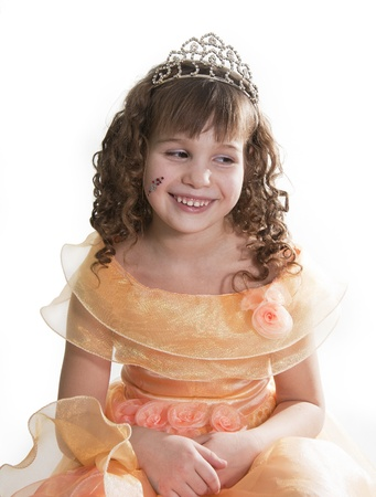 The girl the princess in a orange dress sits opposite to a white background photo