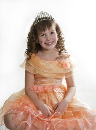 The girl the princess in a orange dress sits opposite to a white background Stock Photo