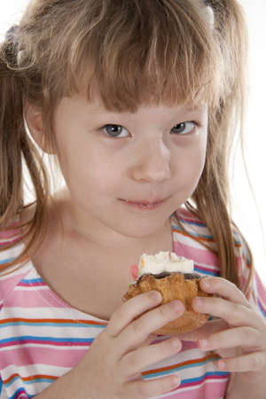 Small girl is eating cake Stock Photo - 8815339