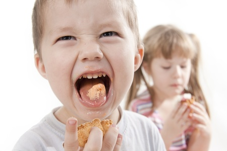 Children eat a cake. Boy grimaces and puts out the tongue photo