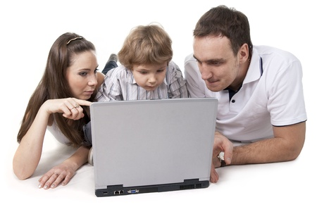 family living: Young family lying on a floor with the computer on white isolation Stock Photo