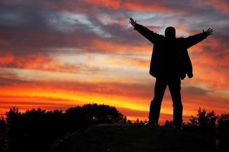 Anbetung des Himmels. Silhouette des Mannes mit Hände nach oben, auf einen Sonnenuntergang