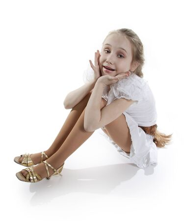 Girl the dancer has sat down to have a rest on a floor. White background photo